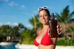 Mulher nas férias de verão que guardam a garrafa da loção para bronzear fotografia de stock royalty free