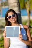 Mulher nas férias tropicais que guardam a tabuleta digital foto de stock