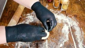Mulher nas luvas pretas que adicionam e que envolvem a carne triturada na massa para fazer a torta com carne ou khinkali vídeos de arquivo