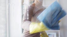 Mulher nas luvas que limpam a janela com o pano
