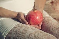 Mulher nas meias brancas do laço que guardam o pomegrante Imagem de Stock Royalty Free