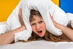 Mulher nas orelhas da coberta de cama com o descanso devido ao ruído fotos de stock