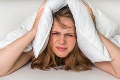 Mulher nas orelhas da coberta de cama com o descanso devido ao ruído imagem de stock