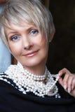 Mulher nas pérolas em seu 40s Fotografia de Stock Royalty Free