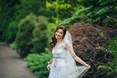 Mulher nas poses brancas no jardim Fotografia de Stock Royalty Free