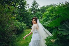 Mulher nas poses brancas no jardim Fotos de Stock Royalty Free