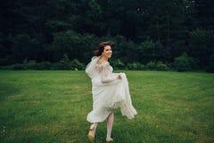 Mulher nas poses brancas no jardim Imagem de Stock