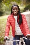 Mulher negra adulta nova que senta-se em uma bicicleta do vintage em um parque que sorri à câmera, vista dianteira, fim acima imagens de stock royalty free