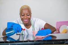 A mulher negra afro-americano bonita e feliz nova na borracha de lavagem veste a cozinha home da limpeza com o sorriso de pano al fotos de stock royalty free