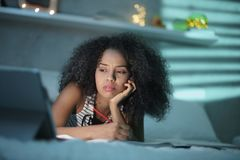 Mulher negra cansado que estuda em casa com PC do portátil fotografia de stock royalty free