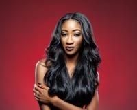 Mulher negra com cabelo brilhante luxuoso longo imagem de stock