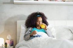 Mulher negra com gripe e o saco de gelo guardando frio imagem de stock