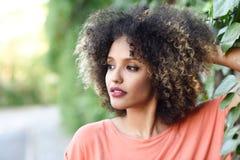 Mulher negra com o penteado afro que está em um parque urbano Fotografia de Stock Royalty Free
