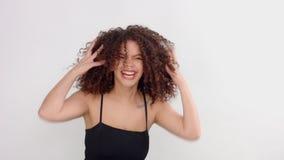 Mulher negra da raça misturada com sardas e cabelo encaracolado no estúdio nas poses brancas a uma câmera filme