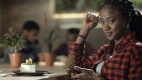 Mulher negra de sorriso com o telefone no café vídeos de arquivo