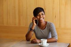 Mulher negra de sorriso que escuta a chamada de telefone celular Fotos de Stock Royalty Free