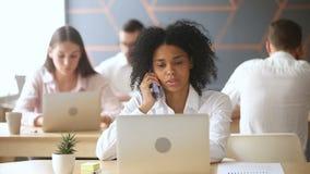 Mulher negra de sorriso que usa o portátil, falando no telefone no local de trabalho