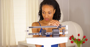 A mulher negra desapontado verifica o peso Fotos de Stock