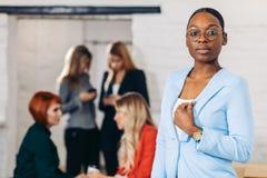 Mulher negra do negócio que ajusta sua roupa em um fundo cinzento fotos de stock