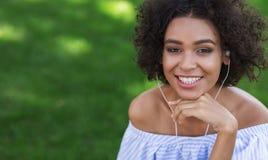 Mulher negra entusiasmado que escuta a música fora fotos de stock royalty free