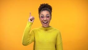 Mulher negra esperta que aumenta o dedo acima, ideia criativa nova, descoberta cient?fica foto de stock