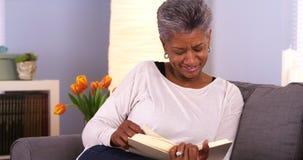 Mulher negra madura que aprecia um bom livro Imagens de Stock Royalty Free