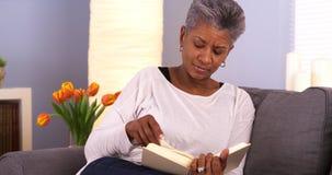 Mulher negra madura que aprecia um bom livro Fotos de Stock Royalty Free