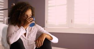 Mulher negra nova atrativa que pensa e que bebe do copo de café Fotografia de Stock