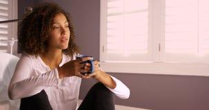 Mulher negra nova atrativa que pensa e que bebe do copo de café Foto de Stock