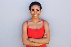 Mulher negra nova bonita que sorri contra a parede cinzenta foto de stock
