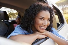 A mulher negra nova de sorriso olha fora de uma janela de carro imagens de stock royalty free