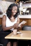 Mulher negra nova entusiasmado que olha na tabuleta Imagem de Stock Royalty Free