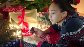 A mulher negra nova está comprando em linha na véspera de Cristmas filme