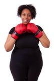 Mulher negra nova excesso de peso que guarda luvas de encaixotamento - peo africano fotografia de stock royalty free