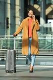 Mulher negra nova feliz do corpo completo que anda na estação com mala de viagem e telefone celular foto de stock royalty free