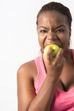Mulher negra nova que morde uma maçã verde Fotos de Stock Royalty Free