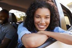 A mulher negra nova que olha fora da janela de carro sorri à câmera imagens de stock