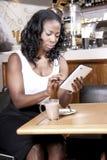 Mulher negra que datilografa em sua tabuleta, coffeeshop Fotografia de Stock