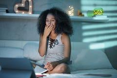 Mulher negra que estuda na noite com laptop imagem de stock