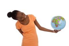 Mulher negra que guarda um globo em suas mãos foto de stock royalty free