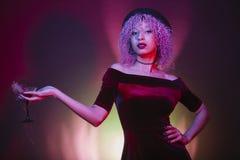 Mulher negra que guarda um martini vermelho com encanto Fotografia de Stock