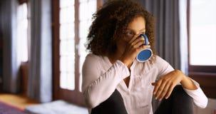 Mulher negra que senta-se apenas em casa com uma xícara de café imagens de stock