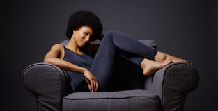 Mulher negra que senta-se no pensamento da cadeira fotografia de stock