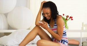 Mulher negra que texting e que ri Imagem de Stock Royalty Free