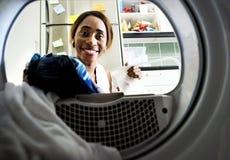 Mulher negra que usa a máquina de lavar que faz a lavanderia Foto de Stock