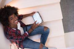 Mulher negra que usa sua tabuleta eletrônica fotografia de stock