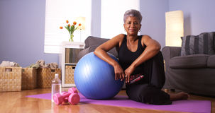 Mulher negra superior que senta-se no assoalho com equipamento do exercício