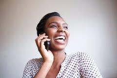 Mulher negra uphappy próxima que ri na conversa telefônica fotografia de stock