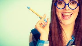 Mulher nerdy feliz na pena de terra arrendada dos vidros Imagens de Stock Royalty Free
