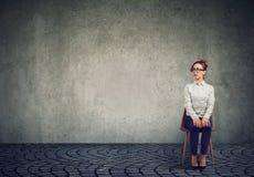 Mulher nervosa nova que senta-se na cadeira fotografia de stock